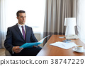 businessman with papers working at hotel room 38747229