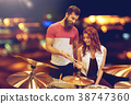 man and woman with drum kit at music store 38747360