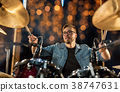 musician playing drum kit at concert over lights 38747631