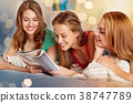 friends or teen girls reading magazine at home 38747789
