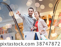 happy young couple with shopping bags in mall 38747872