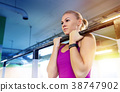 woman exercising and doing pull-ups in gym 38747902