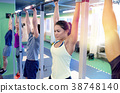 group of people hanging at horizontal bar in gym 38748140
