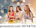 happy friends or teen girls eating sweets at home 38748756