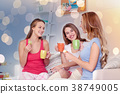 happy young women drinking tea with sweets at home 38749005