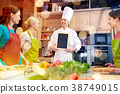 happy women and chef cook with menu in kitchen 38749015