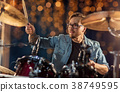 male musician playing drums and cymbals at concert 38749595