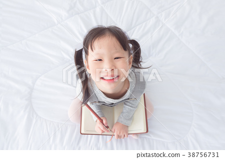 Little girl holding notebook and smiles on bed 38756731