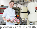 Proud confectioner showing muffins she baked 38760307