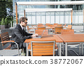 Man in black suit at table and working on computer 38772067
