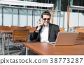 Man in suit at laptop with smart phone smiling 38773287