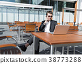 Man in suit at laptop with smart phone smiling 38773288