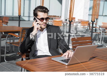 Man in black suit at laptop and talking on phone 38773319