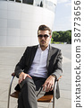 Man in suit sitting on chair near modern building 38773656