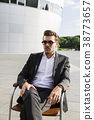Man in suit sitting on chair near modern building 38773657