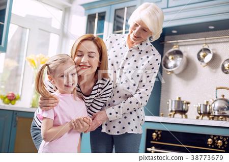 Three generations of women bonding in the kitchen 38773679