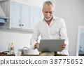 Cheerful male person working at home 38775652