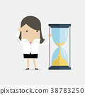 Businesswoman is looking at hourglass with coin. 38783250
