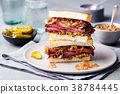 Roast beef sandwich on a plate with pickles. 38784445