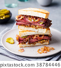 Roast beef sandwich on a plate with pickles. 38784446