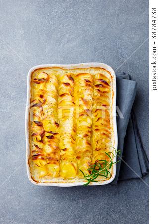 Potato gratin, backed potato slices with sauce. 38784738
