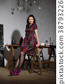 Girl in dress leaning against the table 38793226