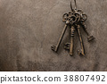 antique keys on old steel metal texture background 38807492
