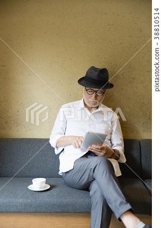 커피를 마시면서 태블릿 PC를 볼 시니어 남자 38810514