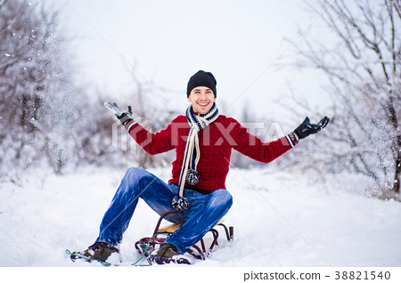 man having fun on a sleigh in snowy weather 38821540