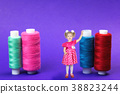 The girl is 3 years standing next to the huge coils of thread on a blue background. 38823244