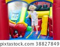 Child jumping on playground trampoline. Kids jump. 38827849