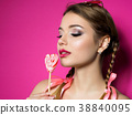 Young beautiful woman holds heart shaped lollipop 38840095