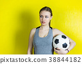 Girl with a soccer ball on a yellow background. 38844182