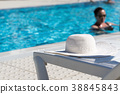 White hat left by a swimming pool with woman 38845843
