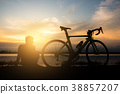 A man sitting beside a bicycle in the morning. 38857207