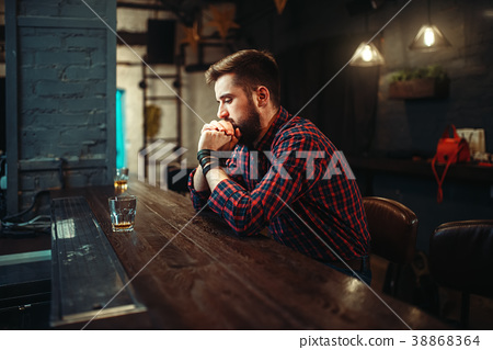 Man sitting at the bar counter and drink alcohol 38868364