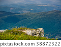 rocky cliff over the valley with rolling hills 38872322
