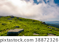 grassy meadow with boulders under the huge cloud 38872326