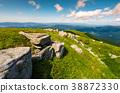 rocky formation on grassy hillside 38872330