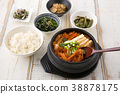 Delicious Korean food - kind of noodles, soup with rice and side dish with fish on the table. 097 38878175