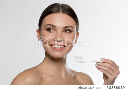 Joyful girl brushing her teeth by special 38888019
