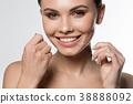 Joyful young woman holding dental floss near mouth 38888092