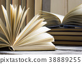 Open book, hardback books on wooden table. Back to 38889255