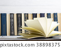 Open book, hardback books on wooden table. Back to 38898375