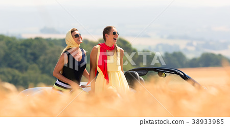 Two women sitting on hood of convertible car  38933985