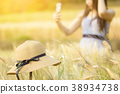 Woman spending summer holiday in barley field 38934738