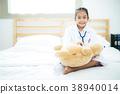 A little doctor girl carrying teddy bear 38940014