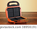 Opened waffle iron closeup on the wooden table 38956191