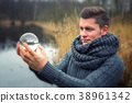 blond man in front of lake holding a glass ball 38961342