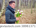 handsome blond man outdoors with tulips 38961371
